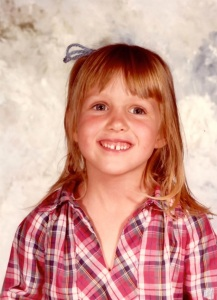 School photograph of the author. A young, pale-skinned girl with long blond hair and bangs, with a yarn bow tied into it. She wears a plaid shirt and is smiling to reveal a gap in her teeth.