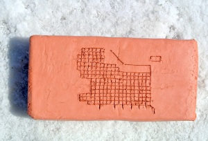 clay brick with the 1860 Zion Plat etched into it. it is sitting on the salt crust of the salt flats.