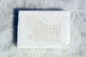 White brick with the 1860 Zion Plat etched into it. it is sitting on the salt crust of the salt flats.