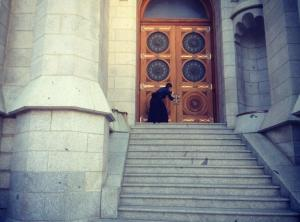 Color photograph of me at the temple door. A woman stands at the top of steps before an oversized door. She wears a black skirt and is kneeling, doing something ambiguous, perhaps testing the lock.