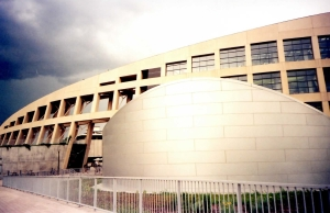 The crescent shaped wall of the Salt Lake City Public Library, with square windows giving a honeycomb appearance, arcing toward the ground. In the foreground is a stainless steel structure with a rounded wall. The building has storm clouds above it. In front is a steel structure that houses the auditorium.