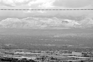 Black and white photograph of the Kenneccott Bingham Canyon Mine from across the valley. It has a light dusting of snow and looks like mountains with the tops removed. Across the top of the image, an electrical wire divides the photograph. Rays of sunshine are shining through the clouds. In the foreground, there are buildings and city streets.