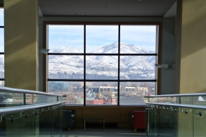 Photograph taken from inside the library looking out one of the crescent wall windows. It perfectly frames the mountains, which are covered in snow. The sky is blue, and the walls are yellow.