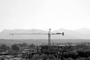 Black and white photograph of a construction crane with the mountains behind it. It's the construction site of the new public safety building.