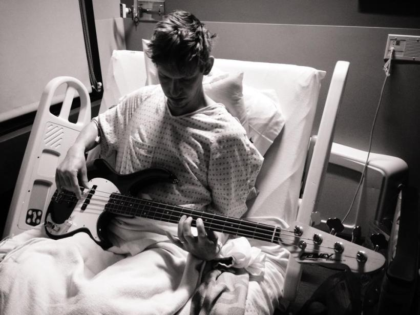 black and white photo of a man seated upright in a hospital bed wearing a dotted gown. He has a bass on his lap and is playing it with some difficulty because of his IV needle. He is looking down at the bass.