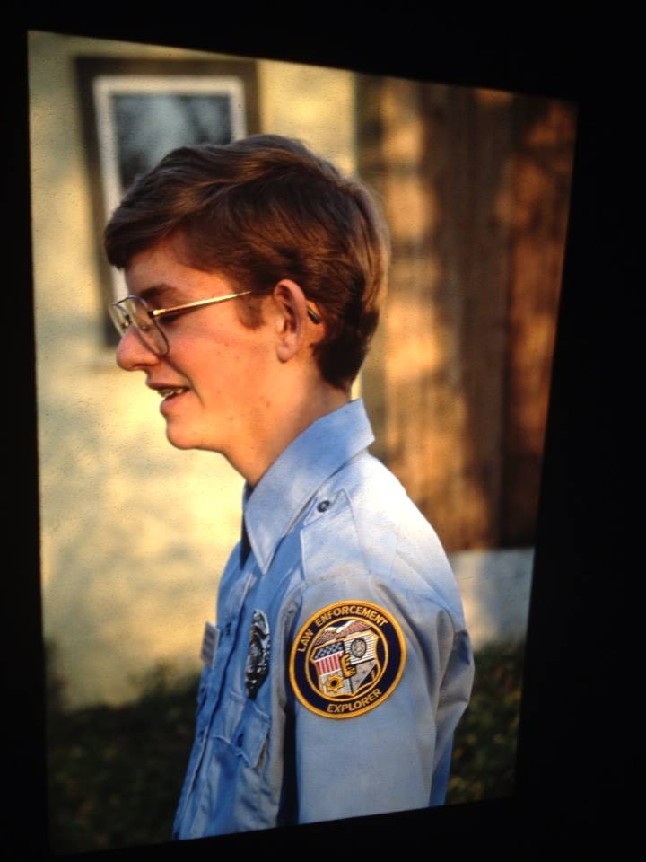 Photo of a young boy wearing a blue oxford shirt with an Ames Law Enforcement Police Explorers patch. He wears square-framed glasses and is standing to the side of the camera, looking down at the ground.