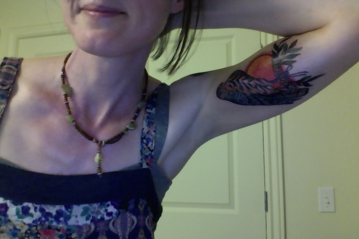 Selfie leaning over with one hand on the back of my head to reveal a falcon tattoo on the inner portion of my arm. There is a bright red sun behind the falcon, who is seated on a branch that doubles as a scroll.