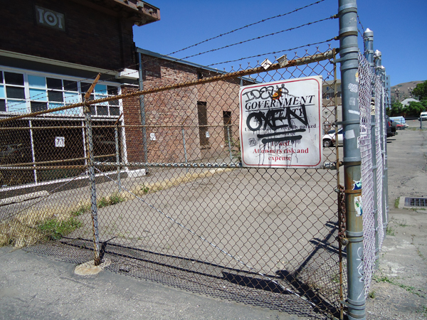 Fence to a government property. OXEN is spray painted on the sign and underlined twice.