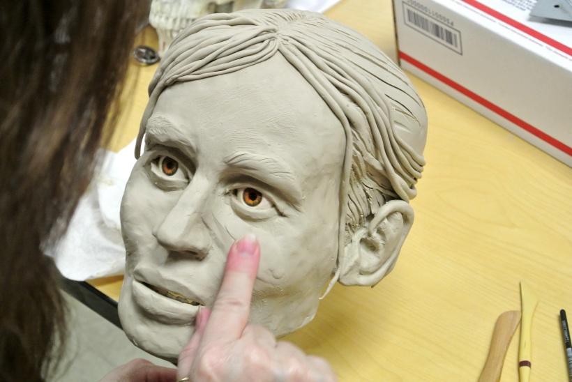 Photo taken from behind and above as Karen T. Taylor smooths some clay onto the sculpture face right below the eyes.