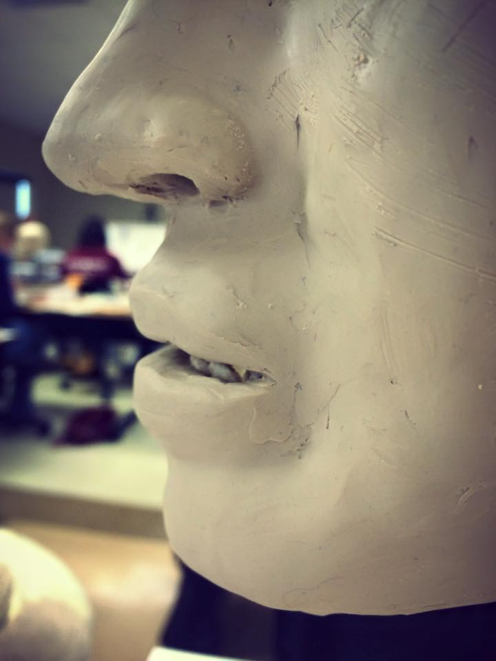 Close-up of sculpture showing nose and mouth. The sculpture's lips are open slightly to reveal teeth. There are hatch marks on the clay surface from using sandpaper to texturize it slightly.