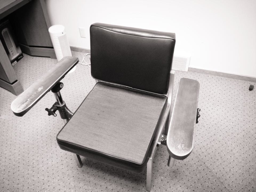 Black and white image of the polygraph chair in which I took my lie detector test. It has very wide-set arms made of wood that is well worn by the many people who have sat in it for tests.