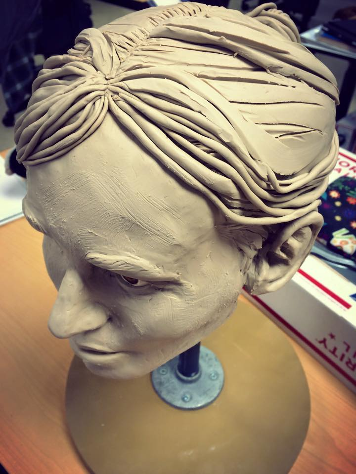 Sculpture from above showing the hair with a less rigid part. The hair has some loose bangs and the rest pulled back into a bun, with a messy part.