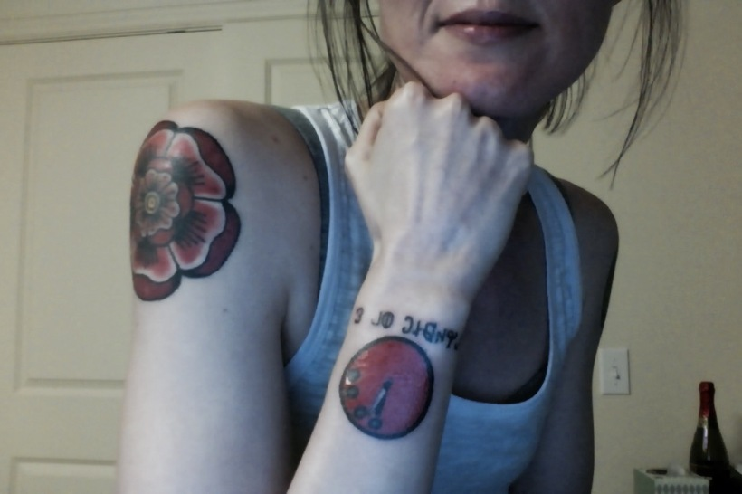 Selfie with my hand under my chin. My doomsday clock tattoo and rose tattoo on my left shoulder are uncovered. Both are bright red.