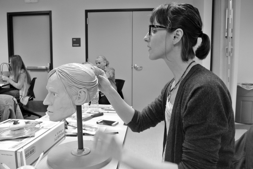 Black and white photo of the author seated behind her sculpture working on the hair.  She is wearing a sweater and glasses and has dakr her hair pulled into a ponytail.