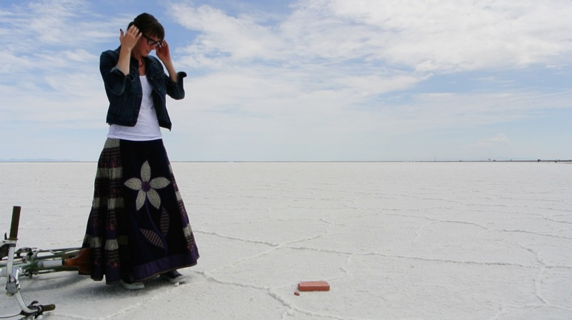 The author standing on the white crust of the Salt Flats with a bicycle tipped over to her right and a clay brick on the ground in front of her. Her hands are touching her temples as she stares down at the brick, apparently in distress. She is wearing black cat-eye glasses, a white shirt, a jean jacket, and a long skirt with a flower on it. The sky is pale blue with clouds.