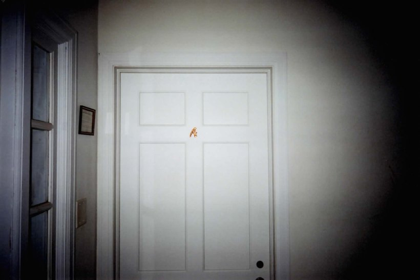 White apartment door with a golden letter A door plate. On the left, there is a window and a framed picture (photo taken too far back to make out detail). The lighting is dark, and there is a black ring around the edges of the image.