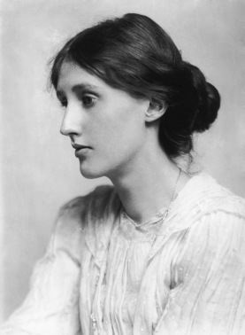 Black and white profile photograph of Virginia Woolf. She is seated facing left, with her long hair in a bun at the nape of her neck. She wears a white, long-sleeved dress. Her mouth is closed, face relaxed, and eyes appear almost unfocused.