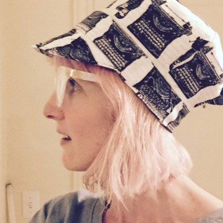 a pale woman with pink hair stands in profile, wearing a white cotton pageboy hat with black vintage typewriters printed on it.