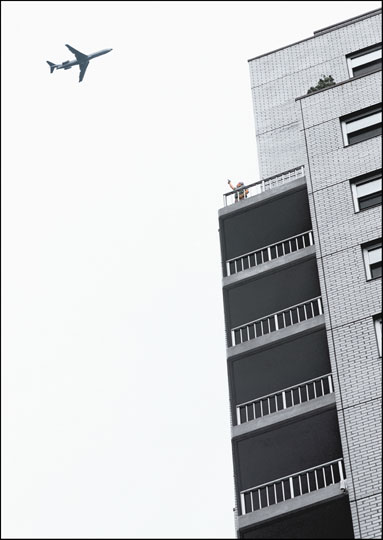 A 747 jet flies low and close to the top of an apartment tower. On a balcony, a person poses with their arm in the air, pointing a gun at the plane.