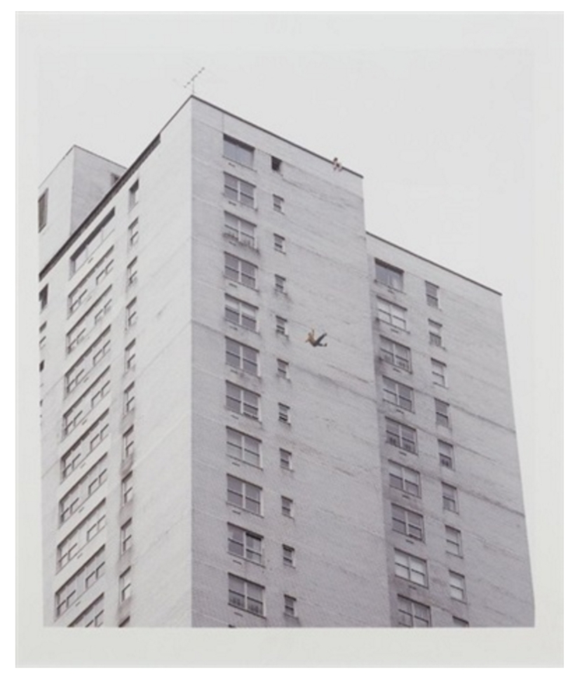 A person falls from atop a tall building, plummeting against a stark white brick backdrop of a modernist structure.
