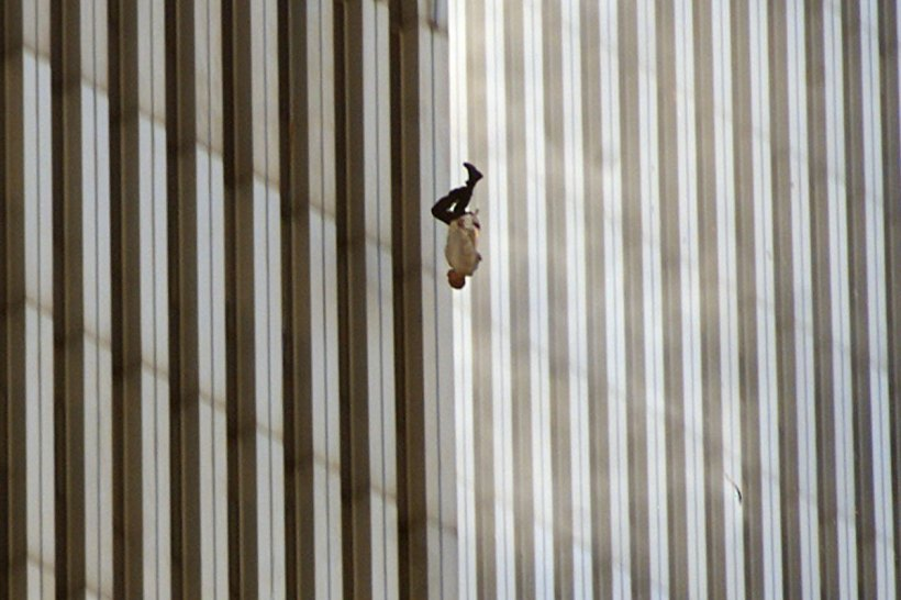 "Famed 9/11 photo of ""falling man,"" in which a man falls from the Twin Towers, face first toward the ground, with one leg bent. Behind him is the repetitive steel structure of the modernist tower."
